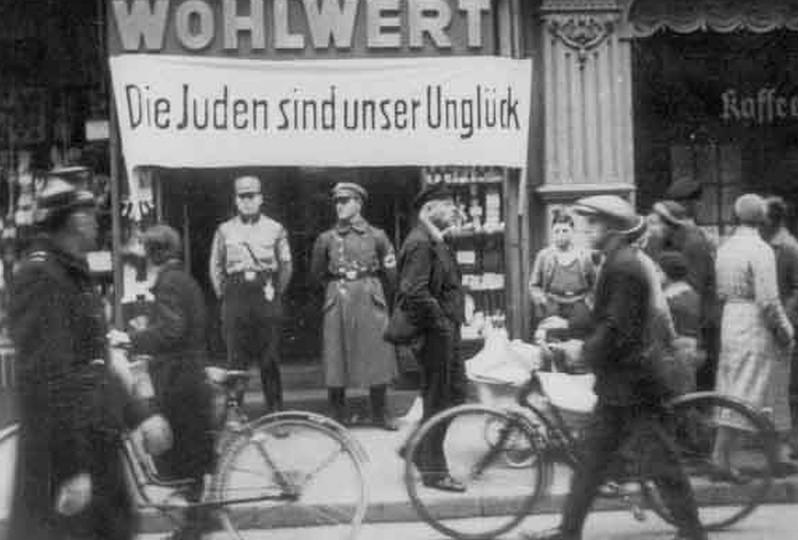 """Spandoek """"De Joden zijn ons ongeluk"""". Op 1 april 1933 organiseren de nazi's in Duitsland een algemene boycot van Joodse winkels. In Heilbronn houden SA-leden de wacht voor de Wohlwertsupermarkt. Heilbronn, Stadtarchiv"""