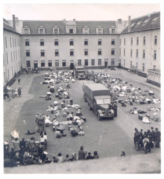 De Dossinkazerne werd eind juli 1942 in gebruik genomen als verzamelkamp. Deze foto dateert uit die periode. Joden, opgeroepen voor 'arbeid in het oosten', wachten tot de kampadministratie hen inschrijft. Mechelen, Kazerne Dossin, Fonds Kummer