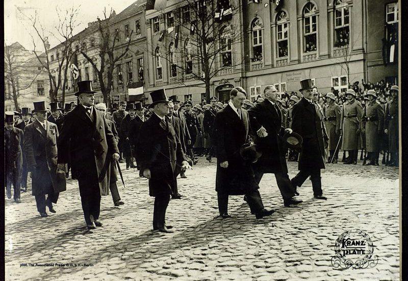 Hitler en de leden van zijn kabinet op weg naar de Garnizoenskerk in Potsdam, waar het nieuw verkozen Duitse parlement wordt geopend. De plechtigheid moet de band tussen het oude Duitse Keizerrijk en het nieuwe nationaal-socialistische Duitsland bezegelen. Foto Georg Pahl, 21-03-1933.