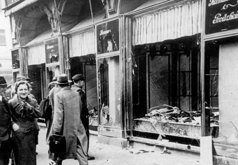 Maagdenburg, na de Kristallnacht van 9–10 november 1938. Een koppel loopt lachend voorbij ingeslagen winkelramen. Koblenz, Bundesarchiv